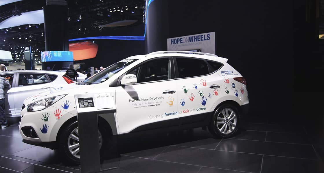 A side view of white SUV covered by hand's printing and stickers regarding 'Hyundai Hope on Wheels' campaign at 2011 Los Angeles International Motorshow