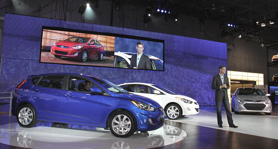 A blue car, a white car and a man making a speech on the show stage with a huge electronic bulletin board reflecting them at 2011 New York International Motorshow