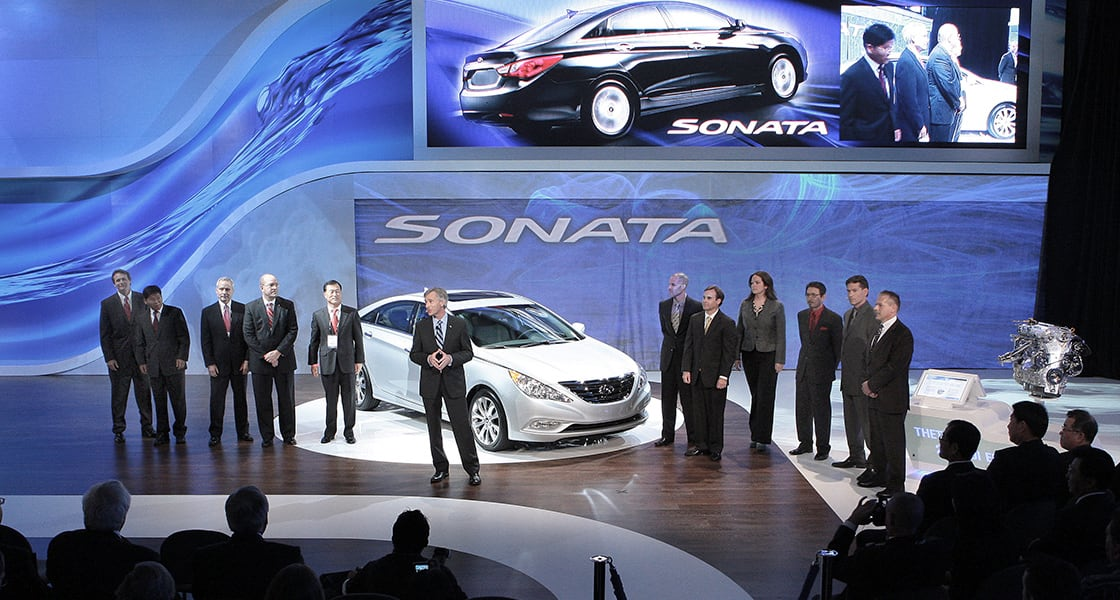 12 people are standing on the stage with a white sonata and a man is making a speech in front of the car at 2011 New York International Motorshow