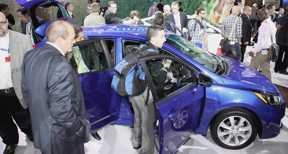 Visitors are trying to have a trial ride with the blue car on show stage at 2011 New York International Motorshow