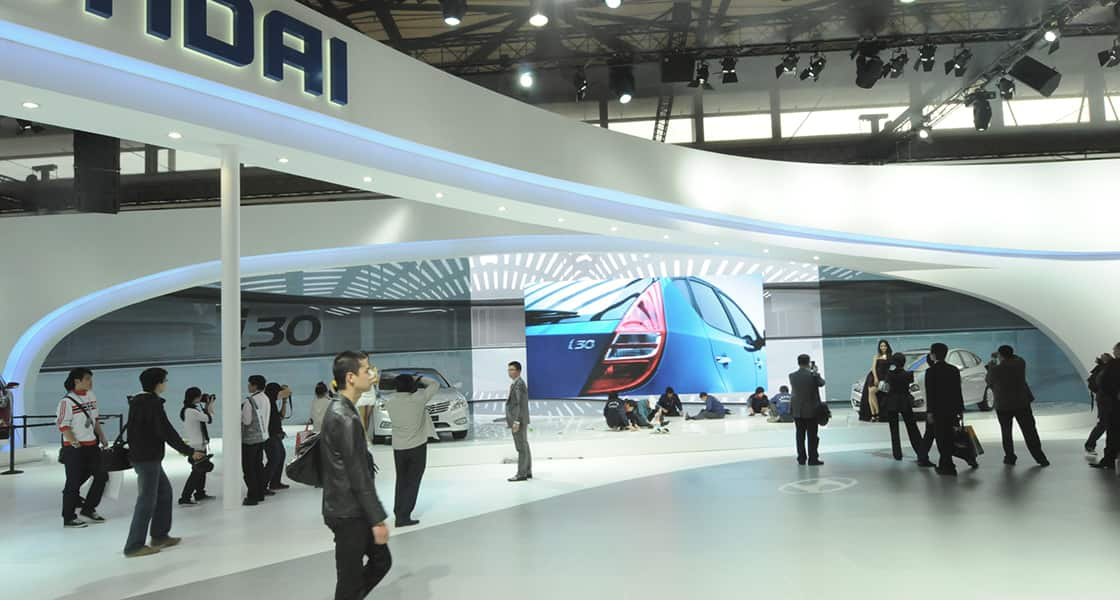 A big screen showing a blue i30 at the hyundai motors venue and in front of the screen people are sitting on the floor at 2011 Shanghai International Motorshow