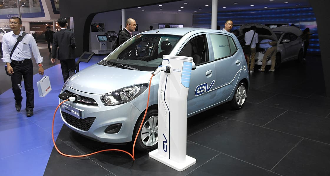 Front-side view of light blue car battery gets refilled at the motor show
