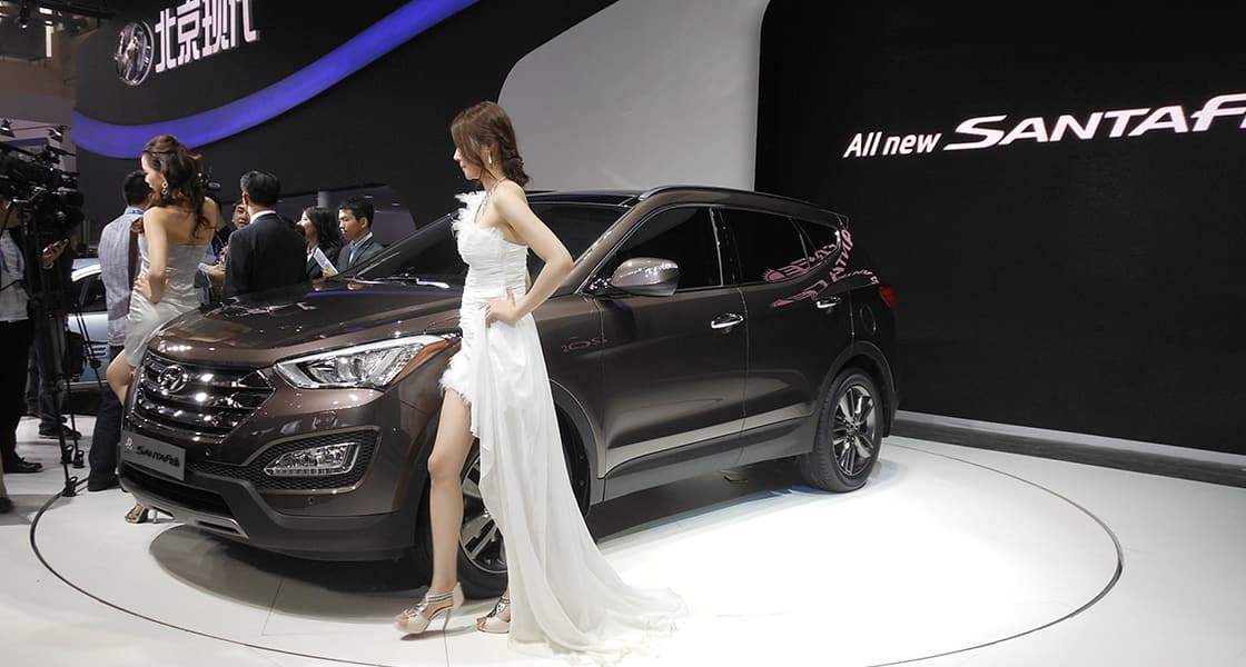 The two models posing next to dark brown Santafe side view exhibited at the 2012 Beijing motorshow