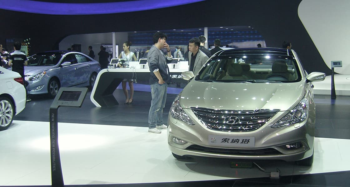 Two people are talking next to light gray car exhibited at the 2012 Beijing motorshow