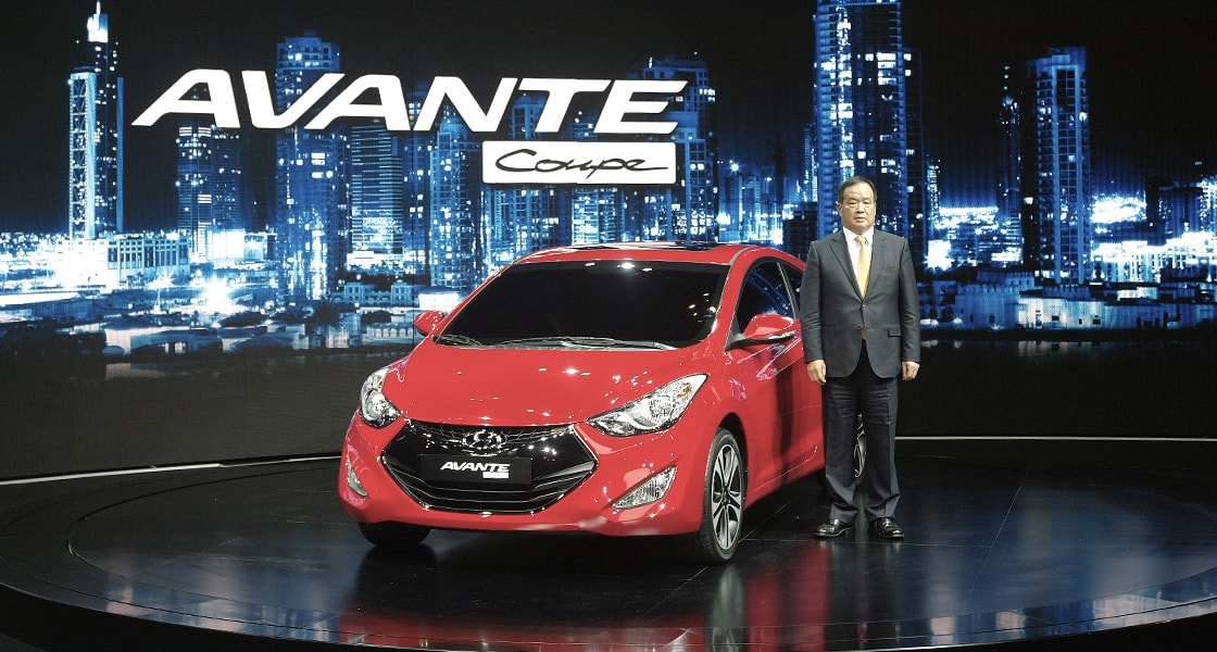 The presenter standing next to red Avante at the stage exhibited at the 2012 Busan motorshow