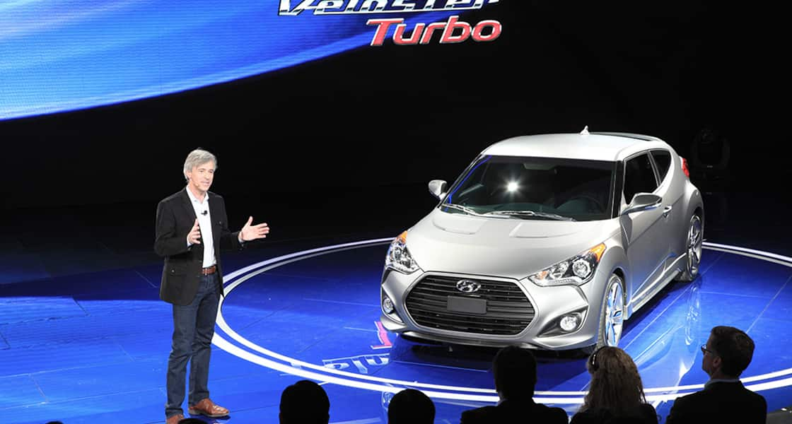The presenter standing next to silver veloster at the stage exhibited at the 2012 Detroit motorshow