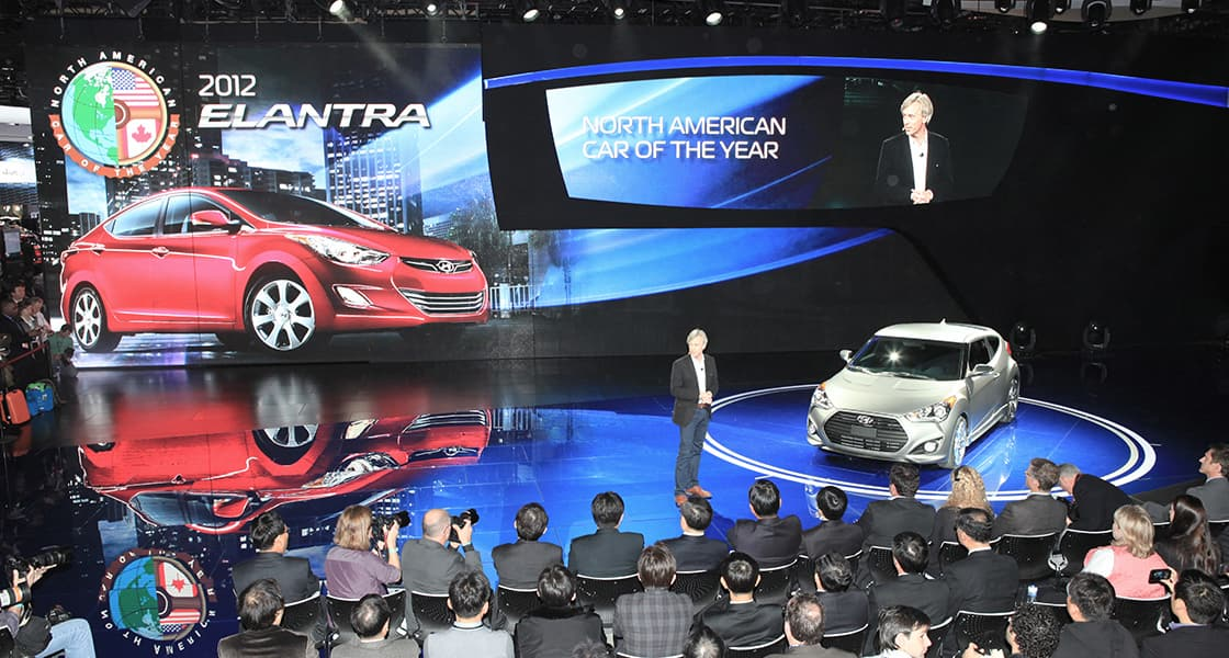 The presenter standing next to white Veloster at the stage with screen showing 2012 Red Elantra at the back wall