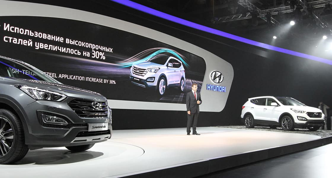 The presenter standing in between white Santafe and light gray Santafe at the stage with screen showing
