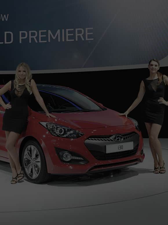 Two models posing next to left side-front view of red I30 at the stage exhibited at the 2012 Paris motorshow
