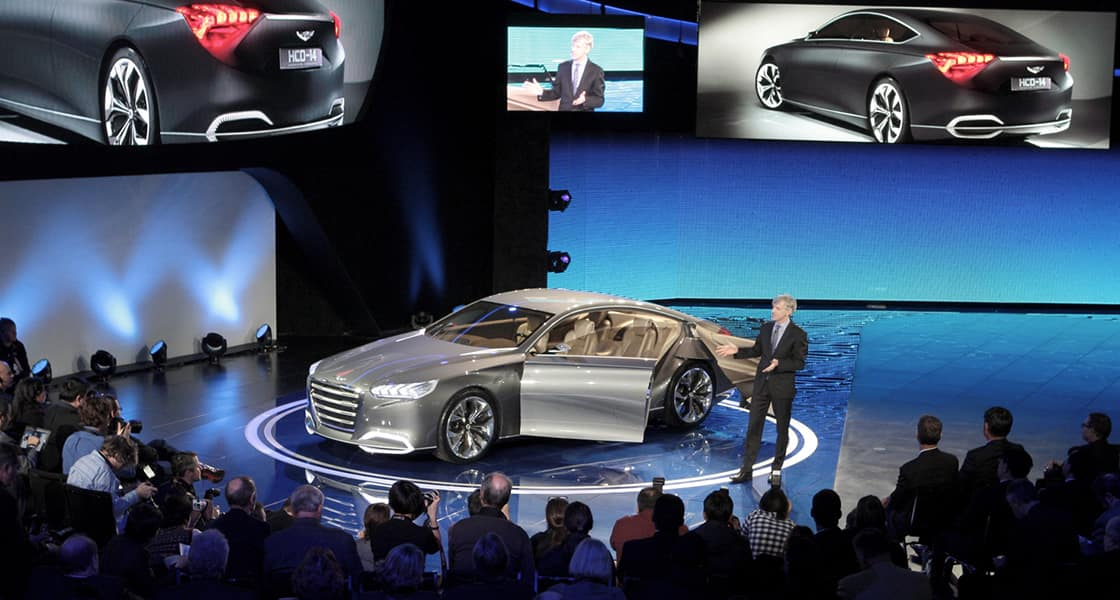 The presenter standing next to gray car at the stage