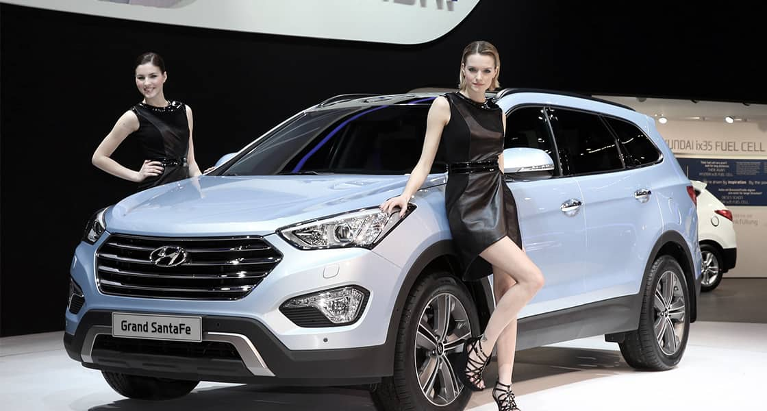 Two models posing next to silver Grand Santafe at the stage