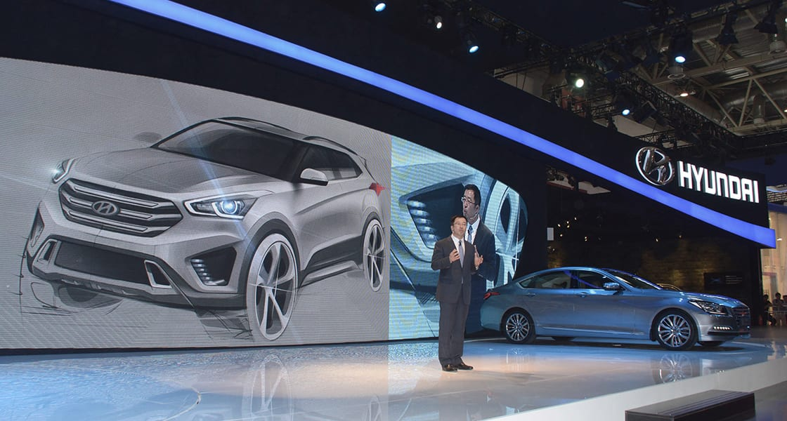 The presenter standing on the stage with car image projected on the background
