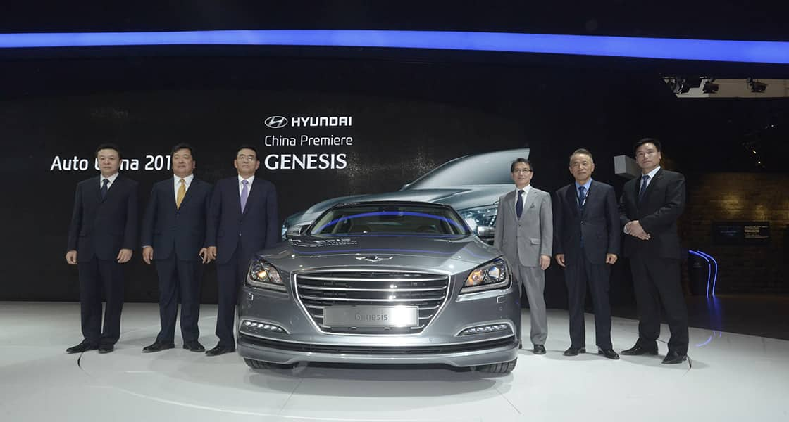 Six men standing next to gray Genesis from the front view