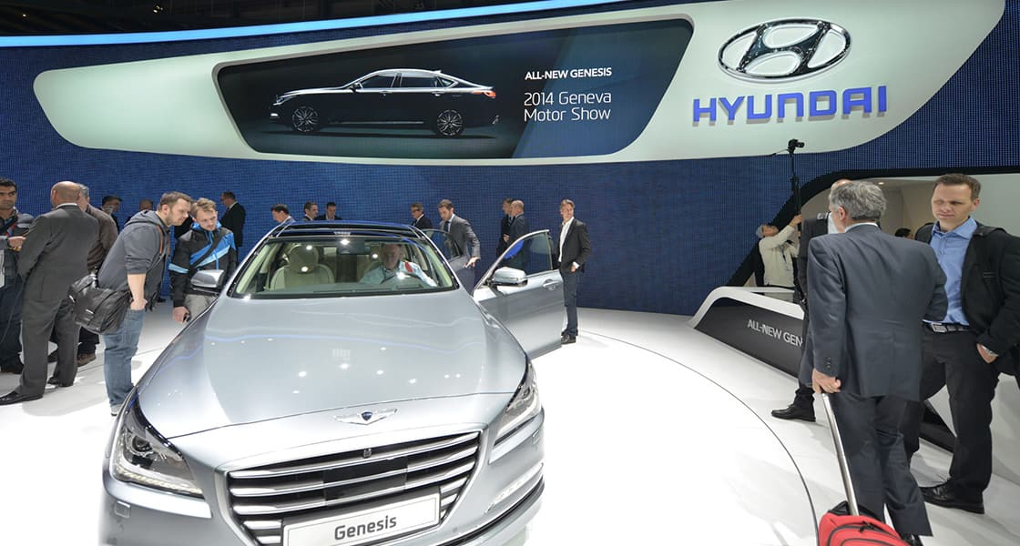 People looking around the genesis's interior and exterior exhibited at the 2014 Geneva motorshow
