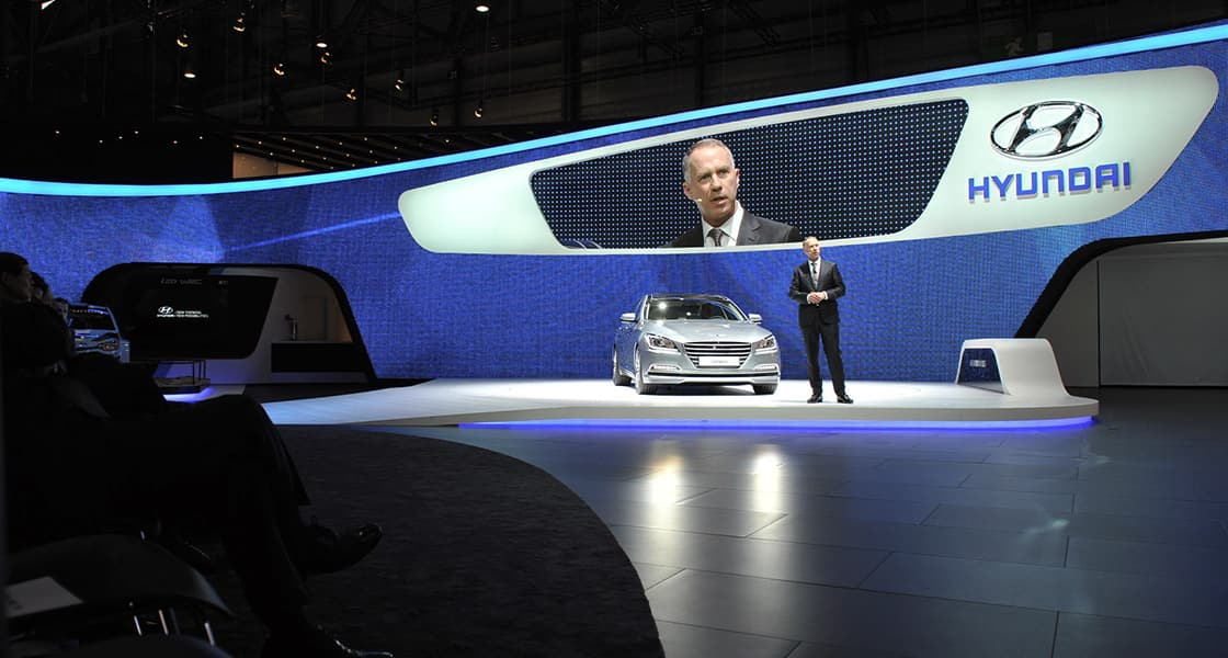 The presenter standing next to gray car at the stage exhibited at the 2014 Geneva motorshow