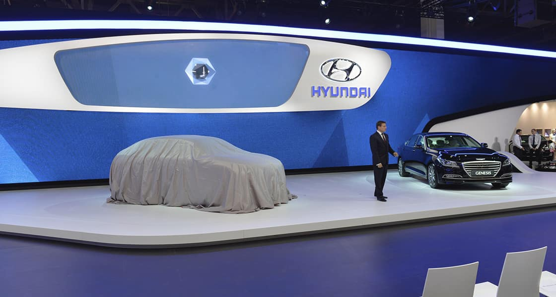 The presenter standing next to the car veiled with gray fabric and black genesis at the stage exhibited at the 2014 Moscow motorshow
