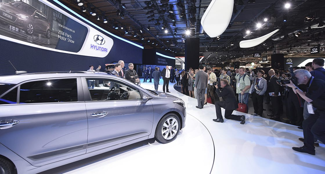 A crowd of people gathered around gray car exhibited at the 2014 Paris motorshow
