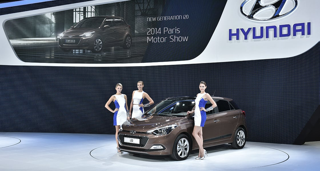 Three blonde models posing in front of brown i20 at the stage exhibited at the 2014 Paris motorshow
