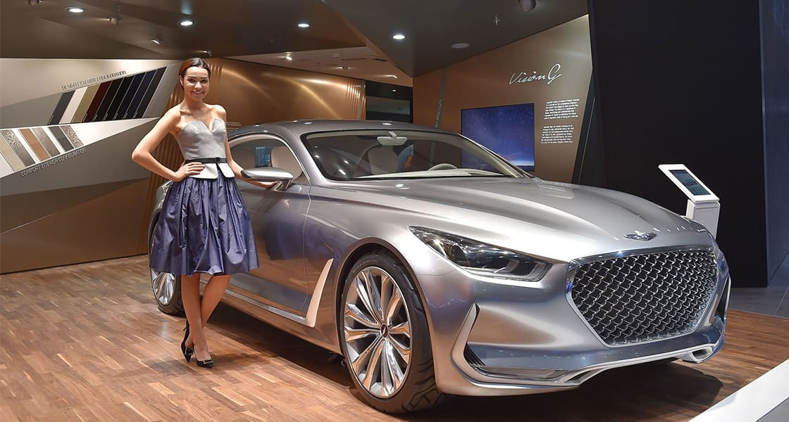 A model wearing purple skirt standing next to silver gray vehicle