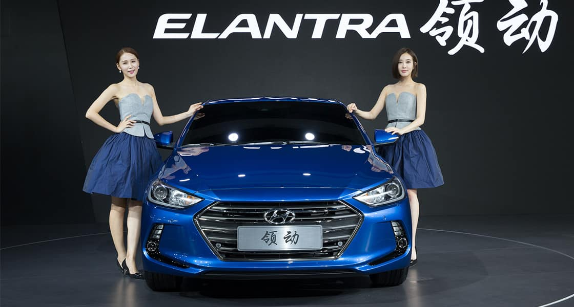 Two models standing right and left side of blue Elantra