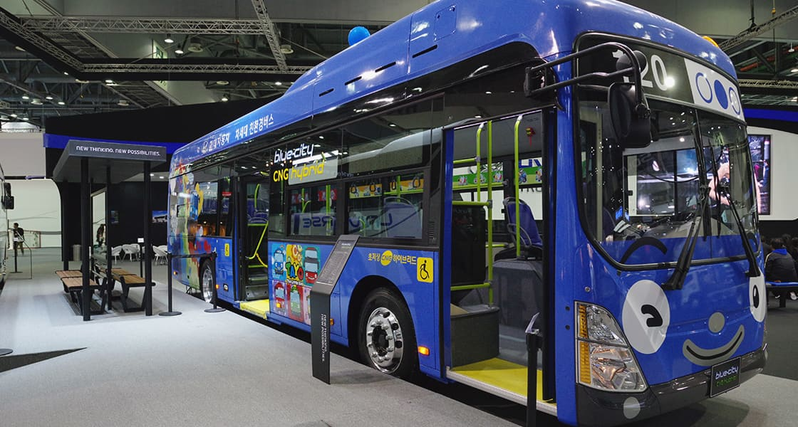 Left side-front view of blue city bus with Tayo character exterior design