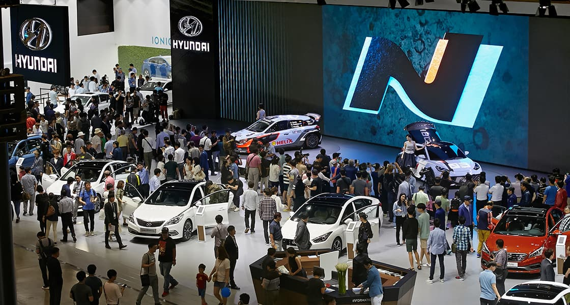 A crowd of people gathered around many cars at the motorshow exhibited at the 2016 Busan motorshow