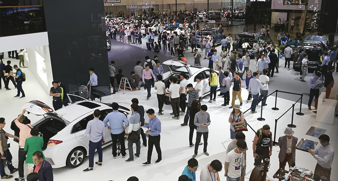 A crowd of people gathered around the car exhibited at the 2016 Busan motorshow