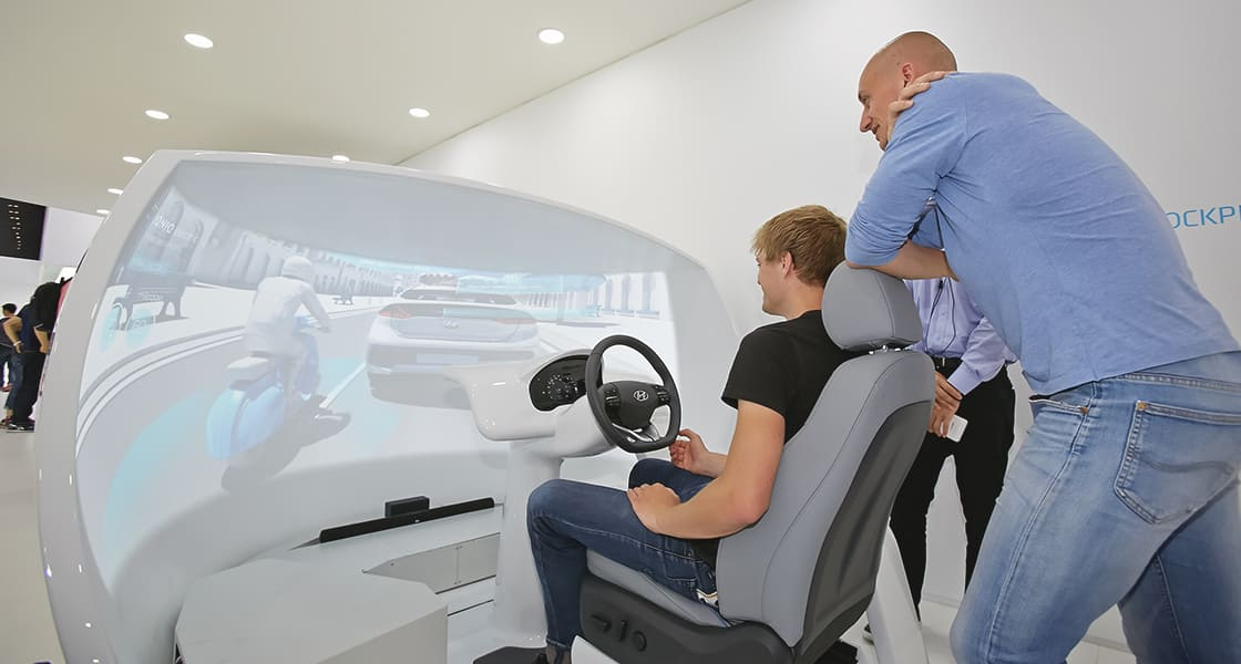 Visitors test-driving on passenger seat of the car exhibited at the 2016 Busan motorshow