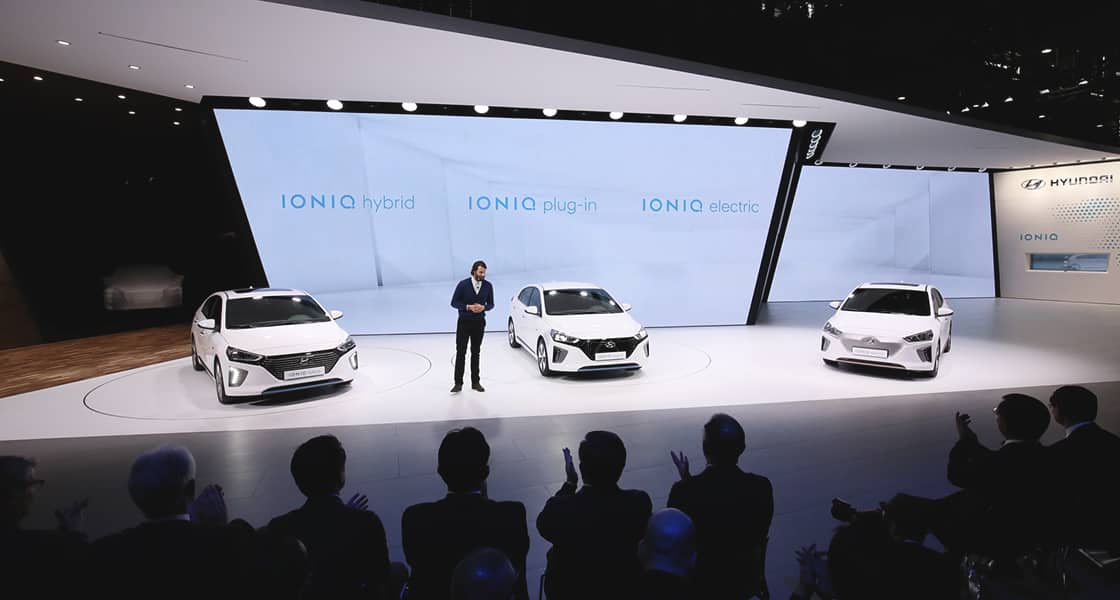 The presenter standing in front of three IONIQ cars at the stage