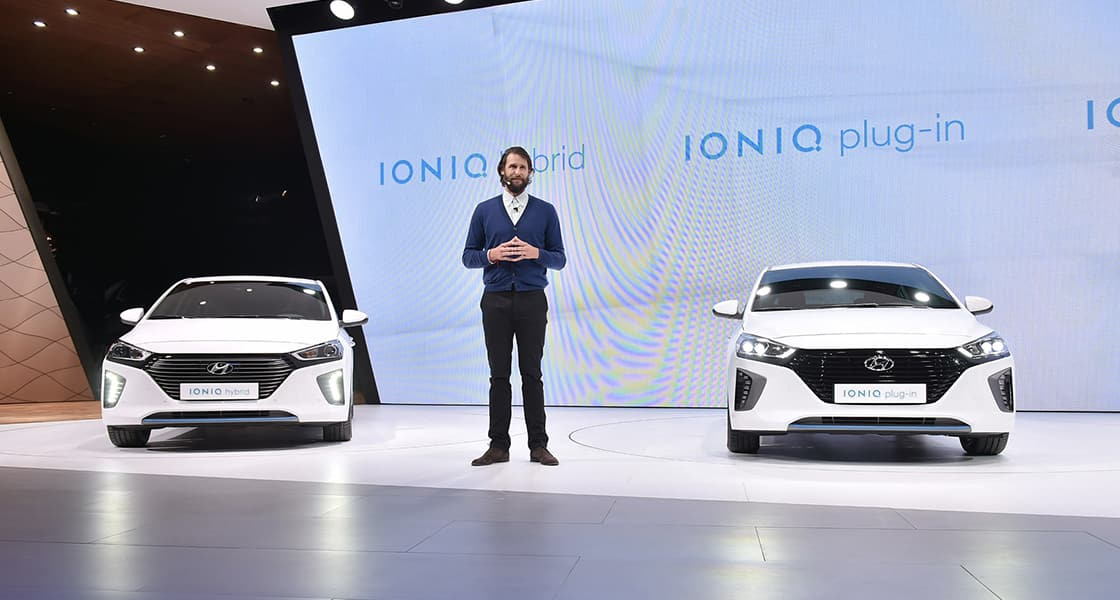 The presenter standing in front of two IONIQ cars at the stage