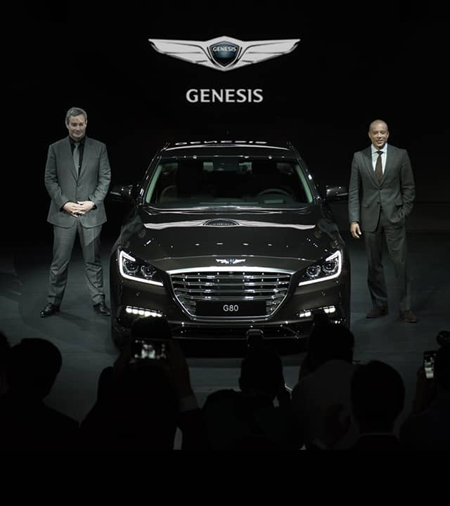 Two men standing next to black genesis from the front view exhibited at the 2016 Busan motorshow