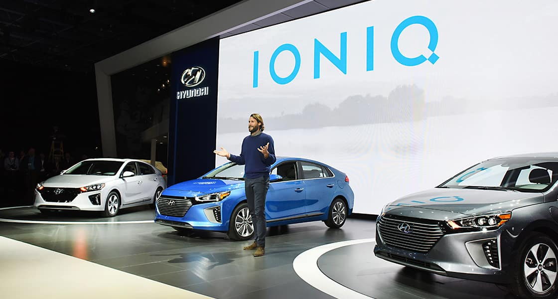 Right side front view of three Ioniq and presenter standing at the stage from the left side viewpoint