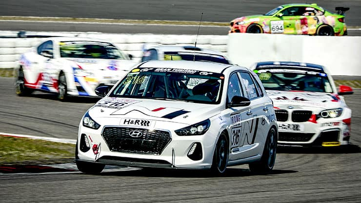 left side front view of i30 N is front of other racing cars on track
