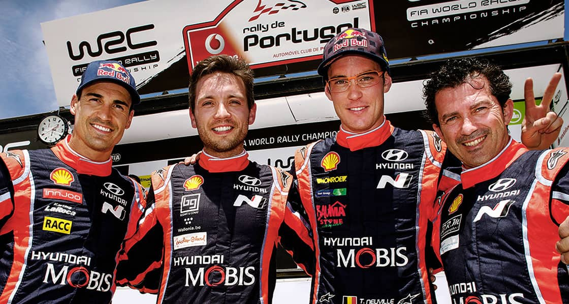 four crews take a group photo in the world rally championship