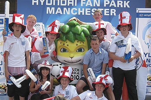 English football fans are posing with Zakumi, at Hyundai Fan Park Photo Zone in Manchester, England