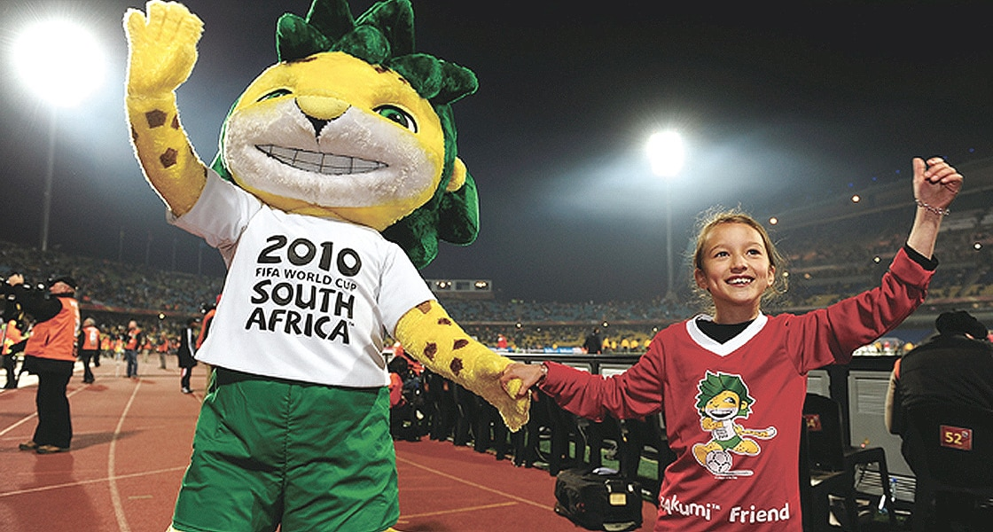 Official mascot of World Cup 2010 'Zakumi' and child are waving to the audience at the stadium