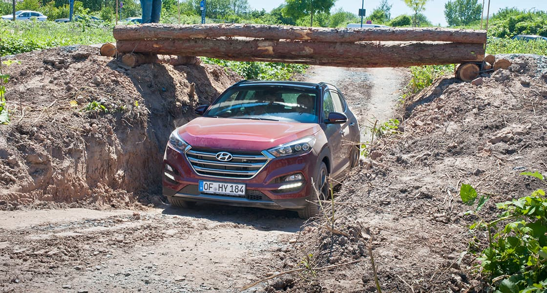 Side-front view of burgundy Tucson driving under the log bridge