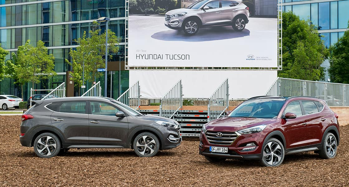 Side-front view of Gray and burgundy Tucsons parked in front of huge advertisement wall showing Tucson model