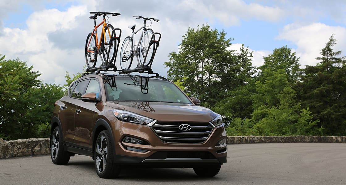 Front view of brown Tucson with two bicycles on the sunroof