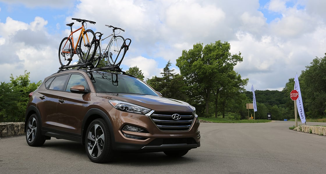 Side view of brown Tucson with two bicycles on the sunroof