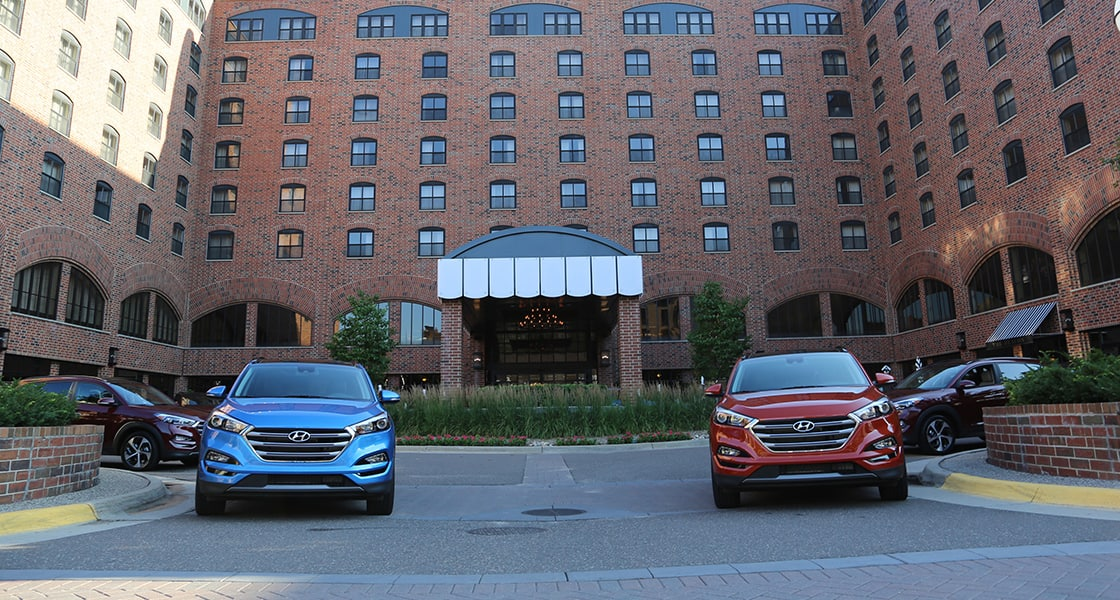 Red Tucson on the right and blue Tucson on the left are driving out from the hotel from the gate