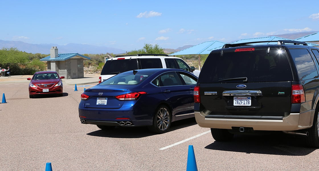 Rear view of two cars parked at the test drive parking lot on a clear day