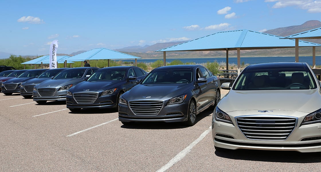 Front view of genesis lined up at the test drive parking lot on a clear day