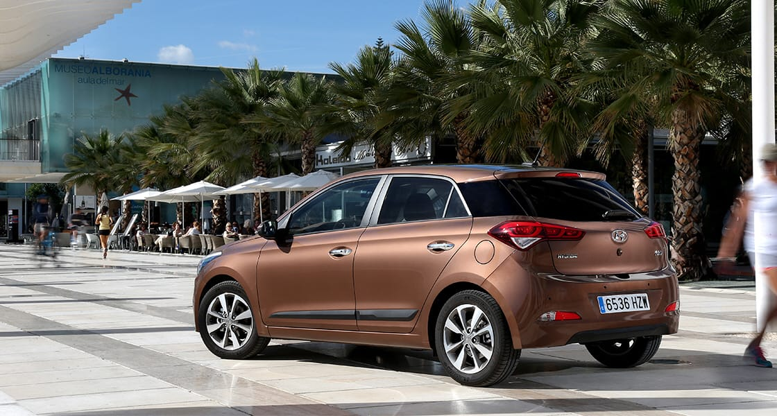 Left side-rear view of brown i30 parked on the marble road with the palm tree beside
