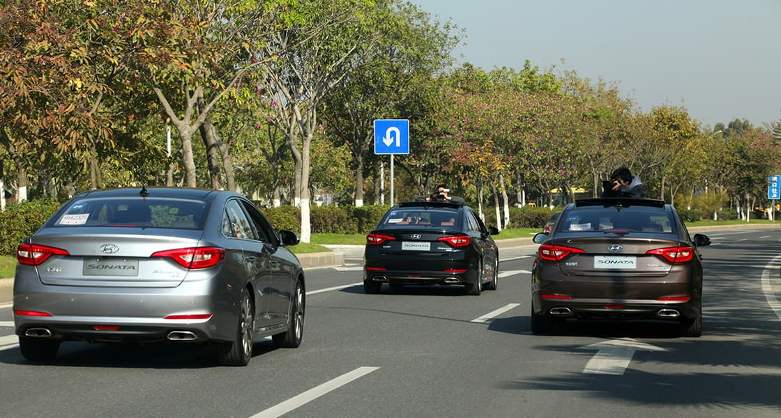 Rear view of three sonata cars driving on the road with the forest beside