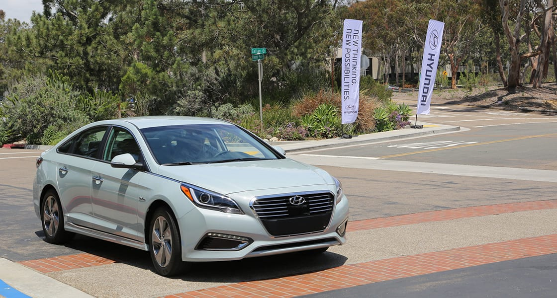 Right-side front view of white Sonata Plug-in Hybrid driving on the street