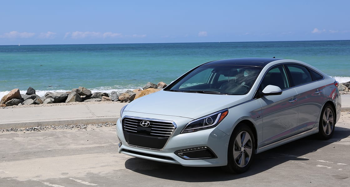 Left side-front view of white Sonata Plug-in Hybrid parked in front of the ocean view