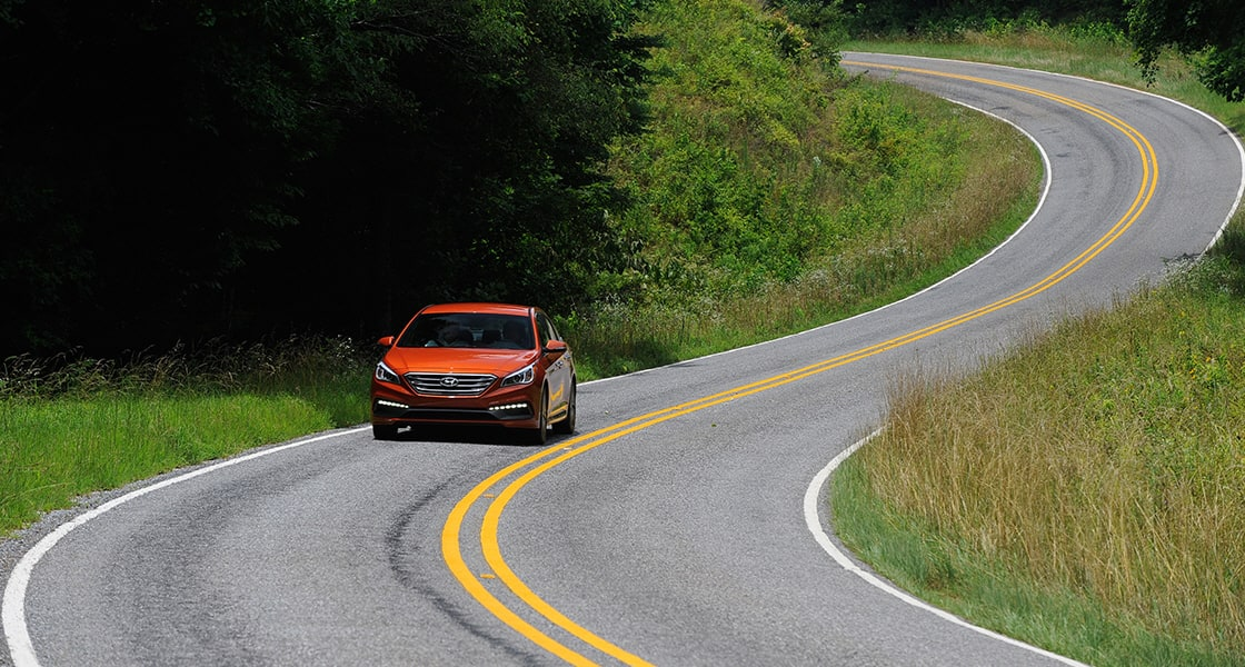Front view of orange sonata driving on curved road with the forest beside