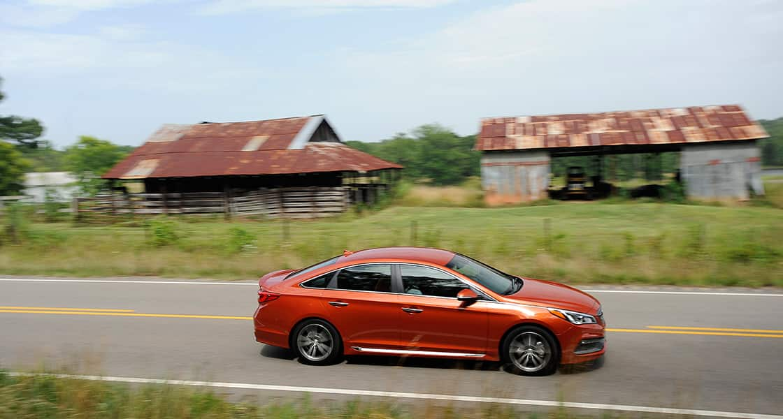 Right side view of orange sonata on the road beside farms