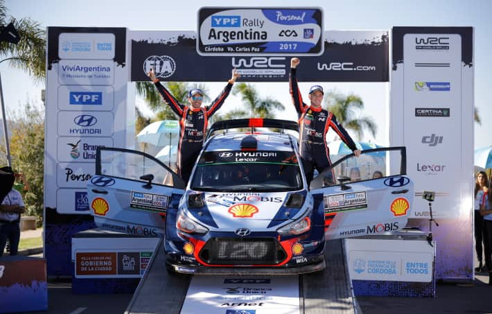 Hyundai Motorsport team members and i20 coupe WRC on the podium